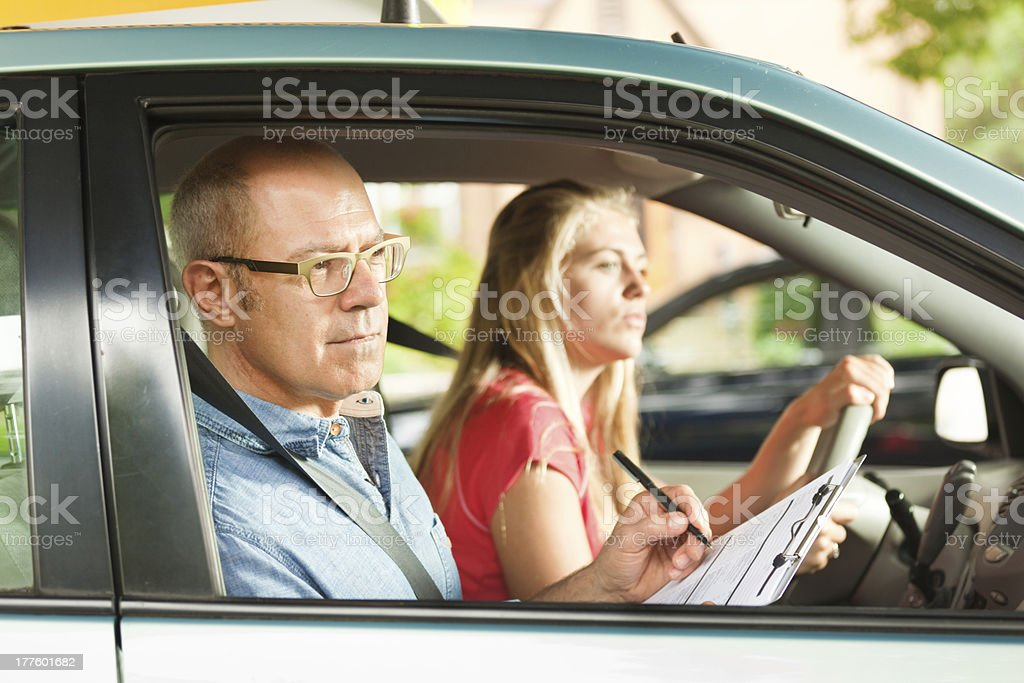 Driver Education Instructor and Examiner with Teen in Vehicle stock photo