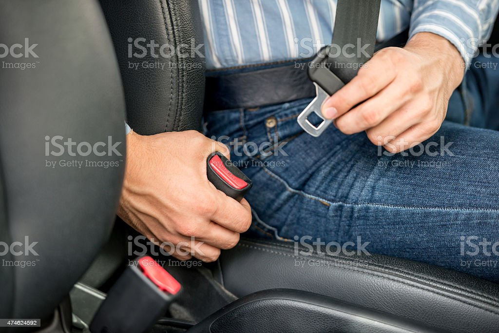 Driver fastening his seatbelt stock photo