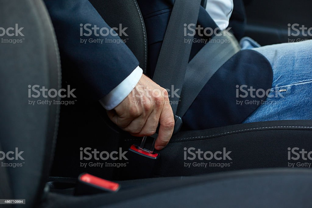 Driver fastens his seat belt stock photo