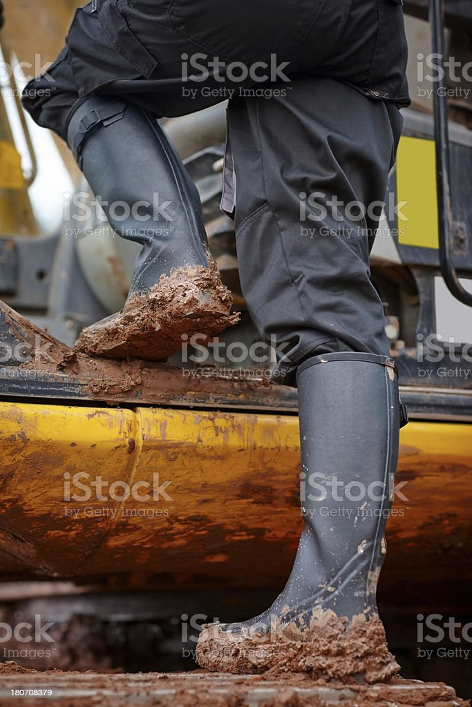 Driver feet full of mud on construction machinery royalty-free stock photo