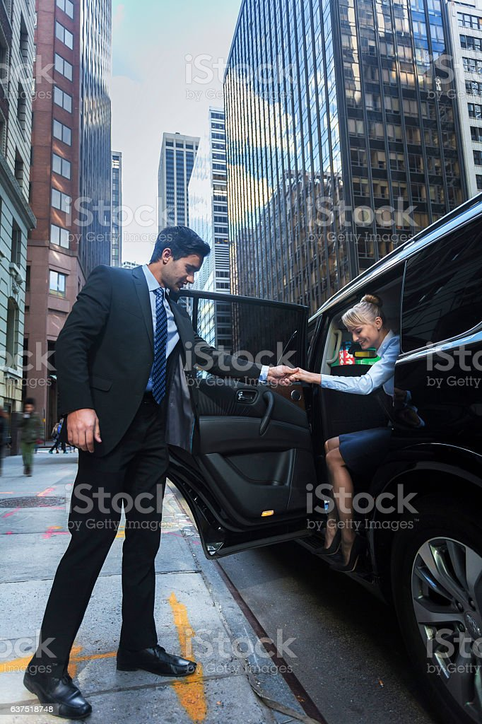 Driver helping passanger out of luxury car stock photo