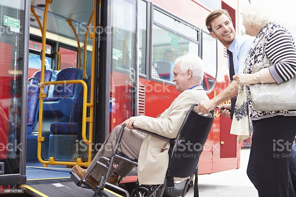 Driver Helping Senior Couple Board Bus Via Wheelchair Ramp stock photo