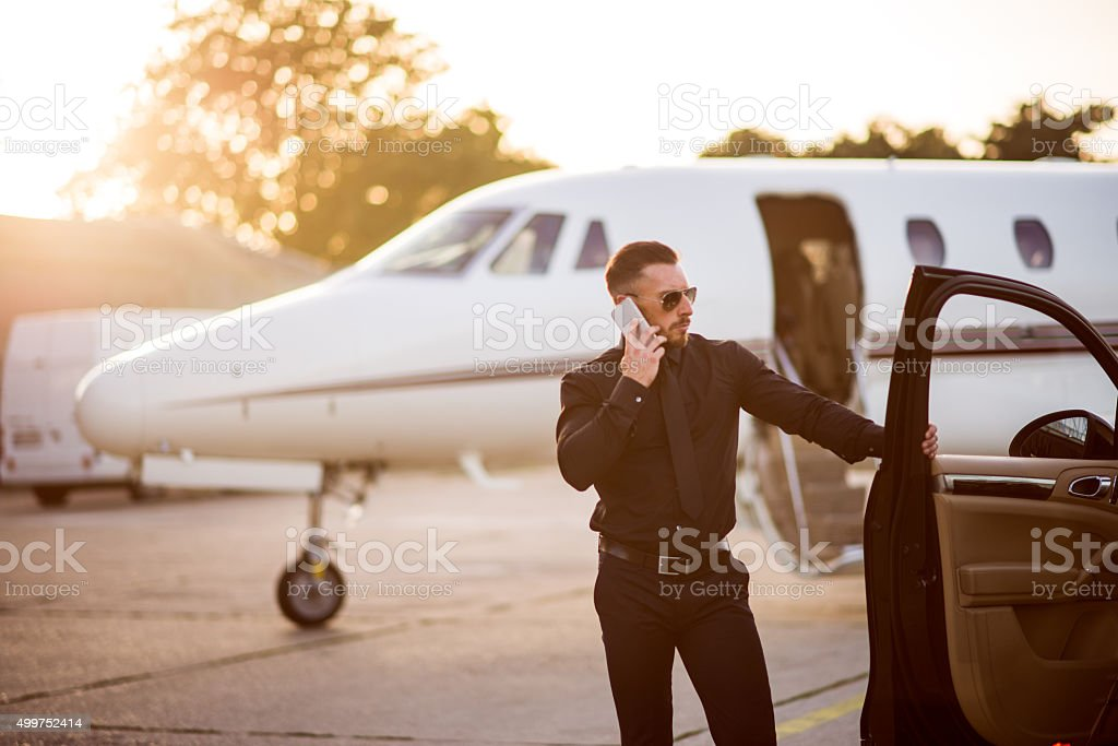 Driver in black suit at the airport stock photo