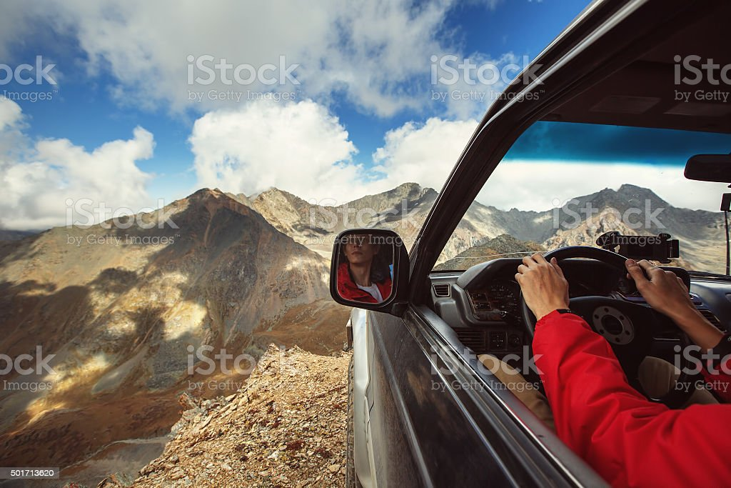 Driver in car on the edge of cliff in mountains stock photo