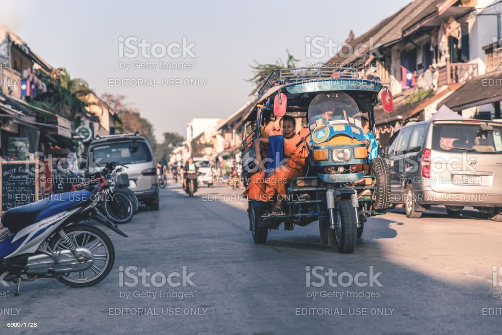 LUANG PRABANG, LAOS - February 16, 2017: Driver in parked tuk-tuk on while carrying young monk in the morning at  Luang Prabang. stock photo