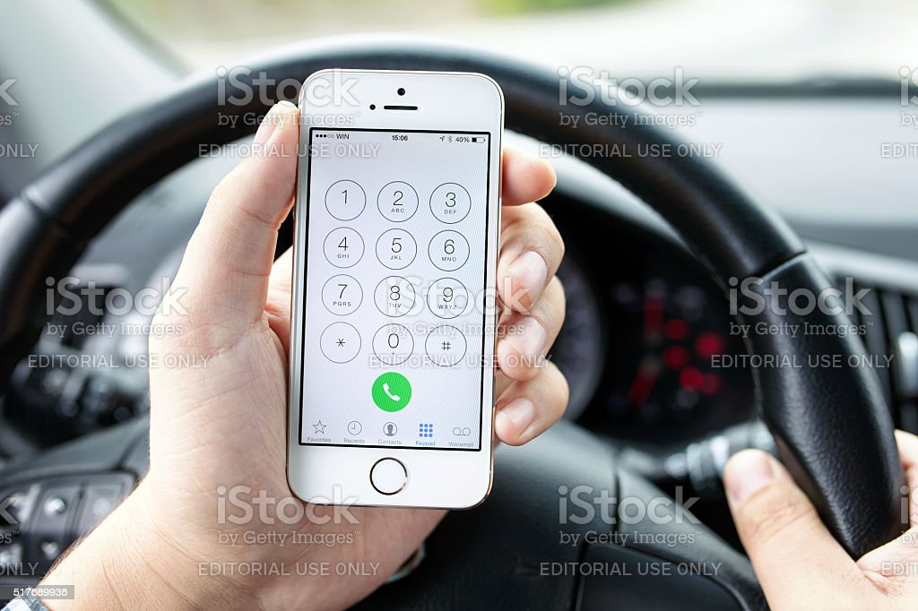Driver in the car dials the number iphone 5s Gold stock photo