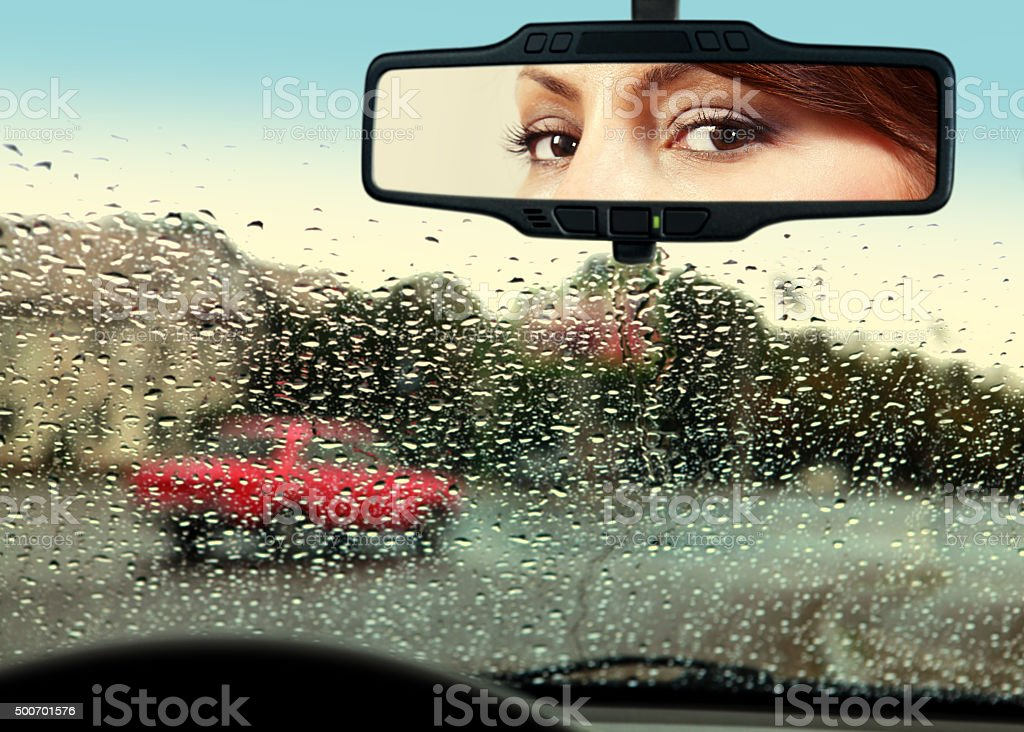 driver looks to rearview mirror stock photo
