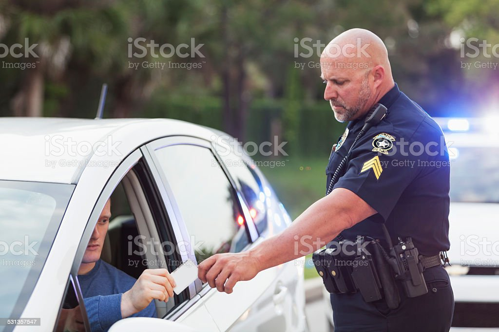 Driver pulled over by police, giving ID to officer stock photo