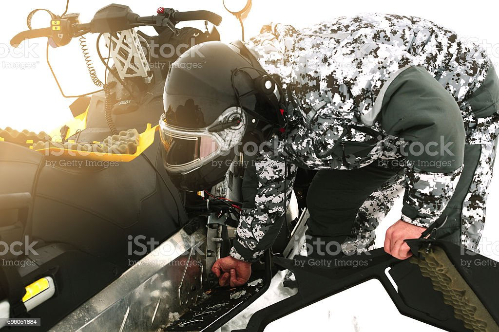 Driver repairing a broken snowmobile. Winter sports. stock photo
