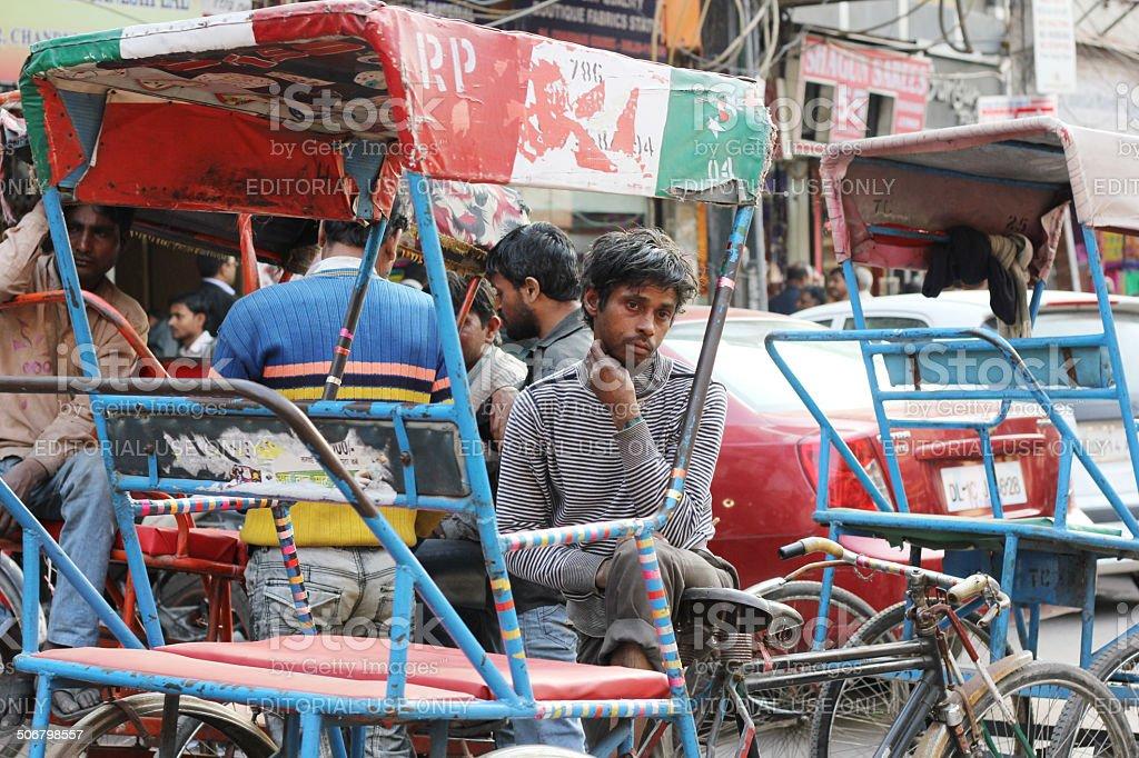Driver rests at cycle rickshaw stand, Delh stock photo