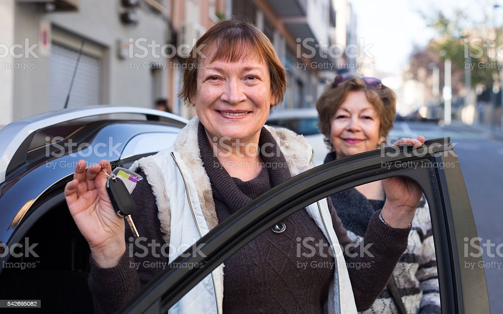 driver standing with car key stock photo