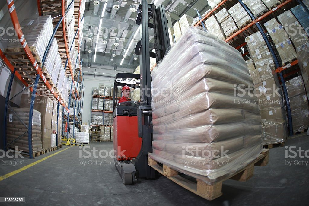 Driver using a forklift in a warehouse stock photo