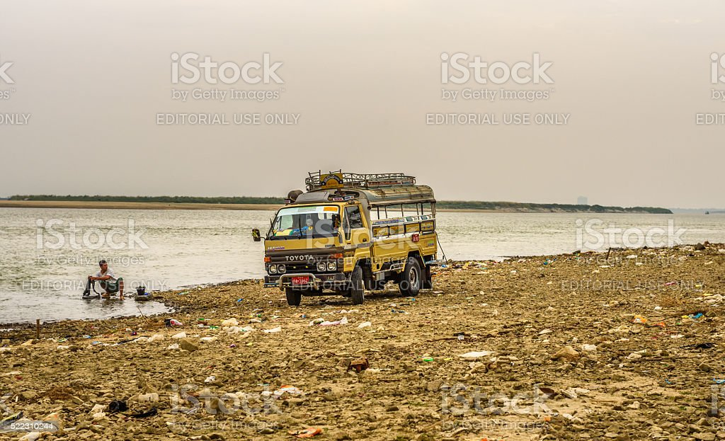Driver washing his car in the Irrawaddy River stock photo