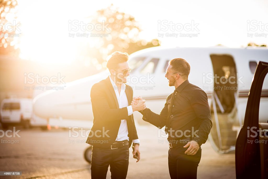 Driver welcoming his boss at the airport stock photo