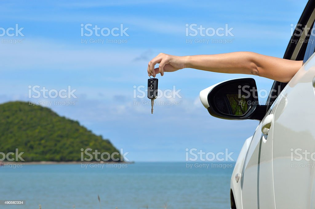 Driver woman happy showing car keys out window stock photo