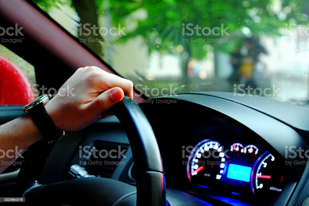 Driver's hand on a steering wheel of a car stock photo