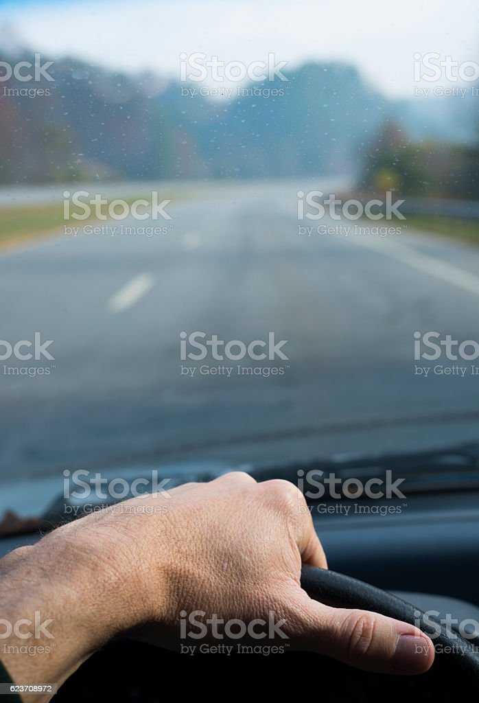 Driver's hand on steering wheel with highway background stock photo
