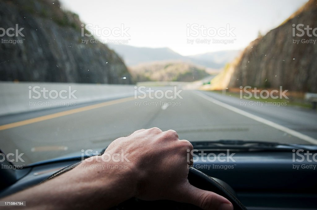 Driver's hand on the wheel driving down highway royalty-free stock photo