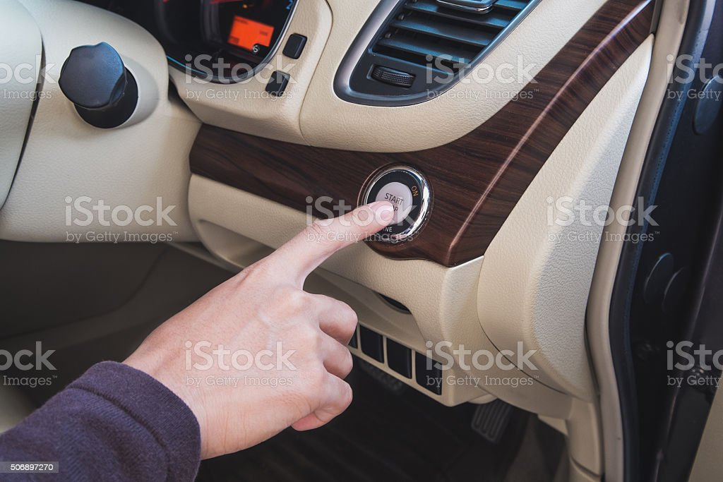 Driver's hand pushing start engine button stock photo