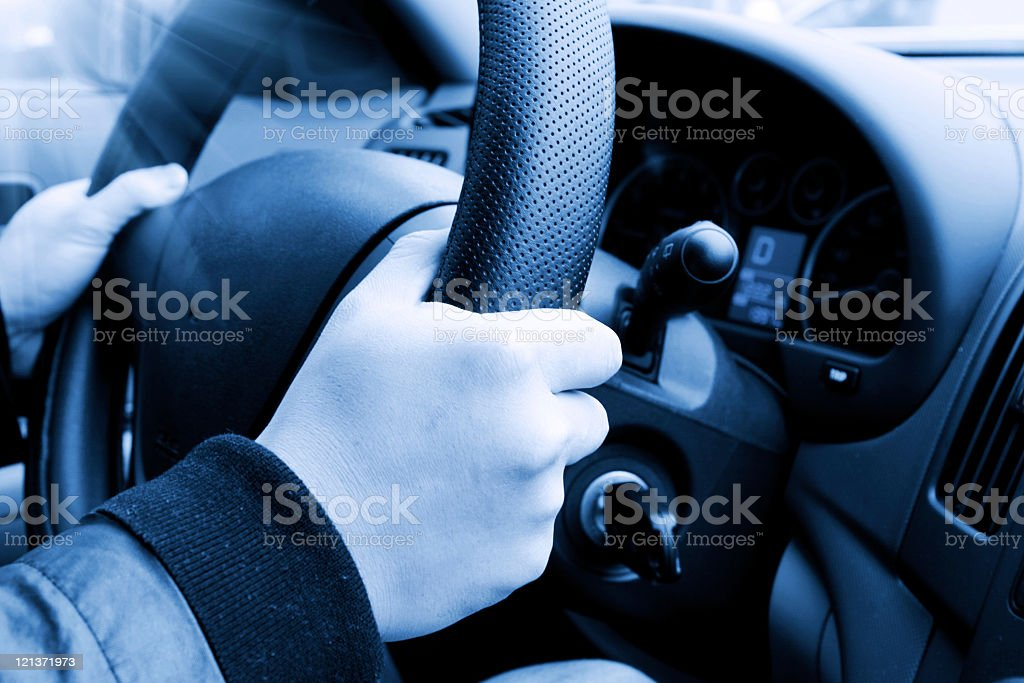 Driver's hands on steering wheel of a car royalty-free stock photo