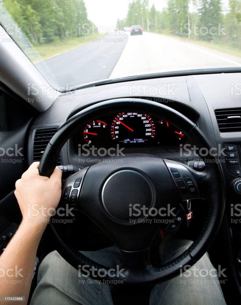 Driver's perspective in a car on a tree lined road stock photo