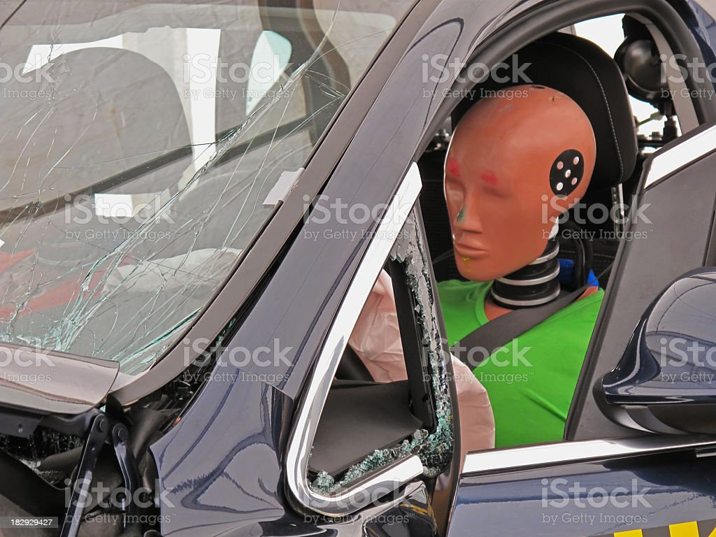 Driver's side view of a car with a crash dummy at the wheel stock photo