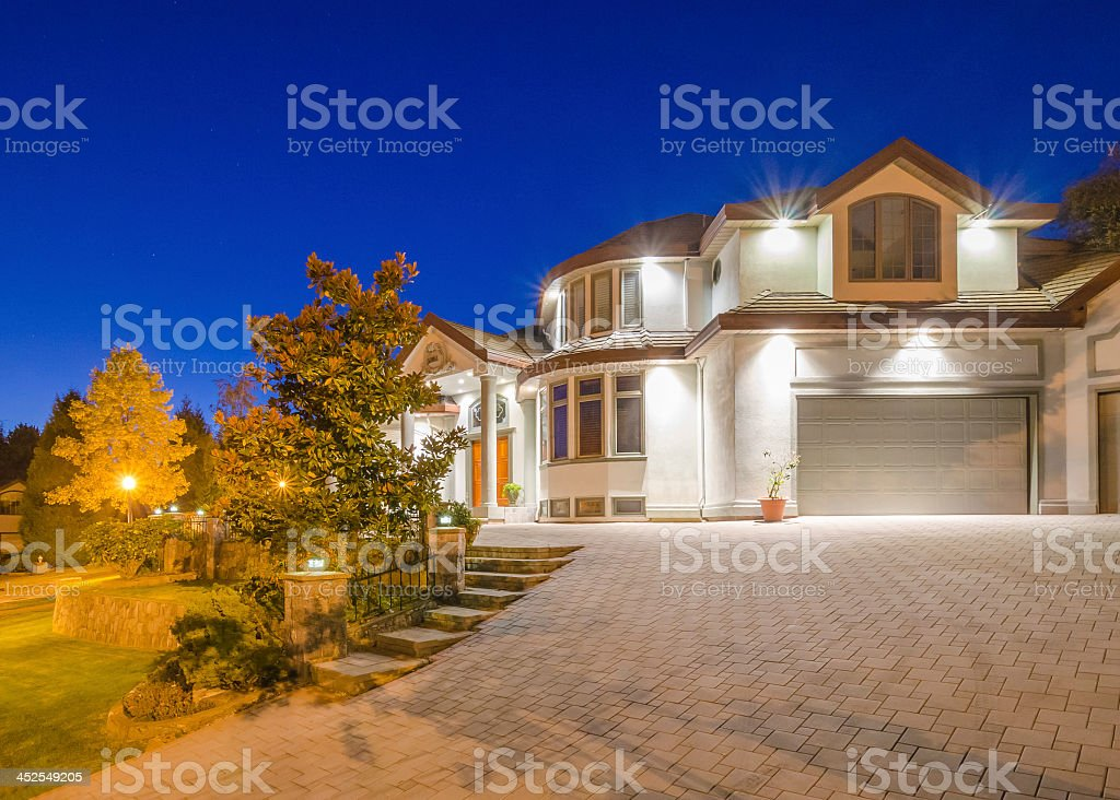 Driveway view of huge house at dusk  stock photo