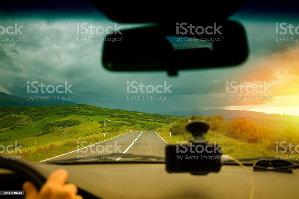 Driving a car in Tuscany valley Valdorcia in stormy weather stock photo