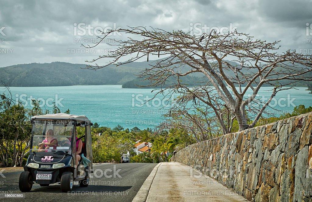 Driving a golf buggy around tropical Hamilton Island, Australia stock photo