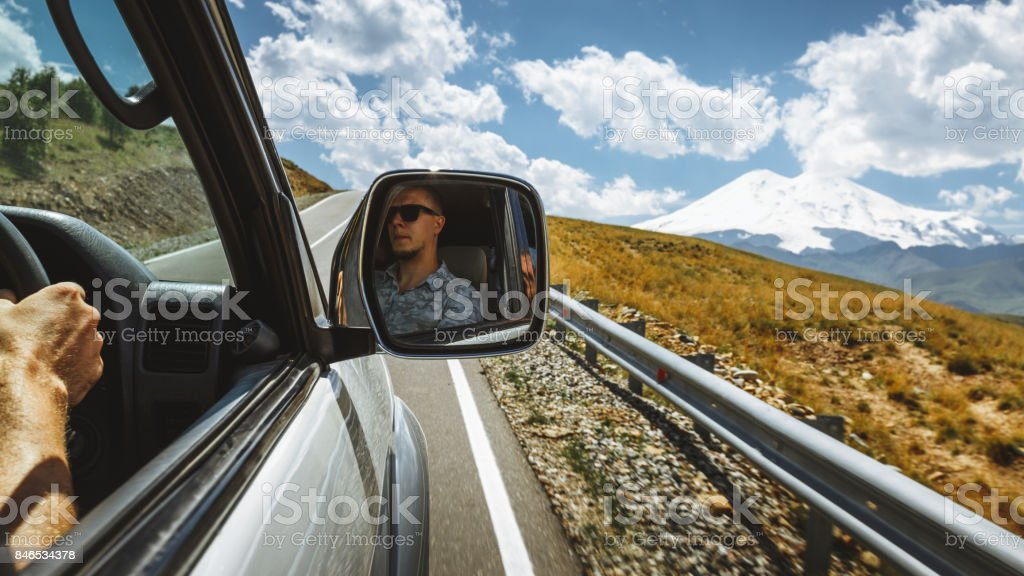Driving At Mountain Road. Driver In A Car Side Mirror. Road Trip Journey Lifestyle Concept stock photo