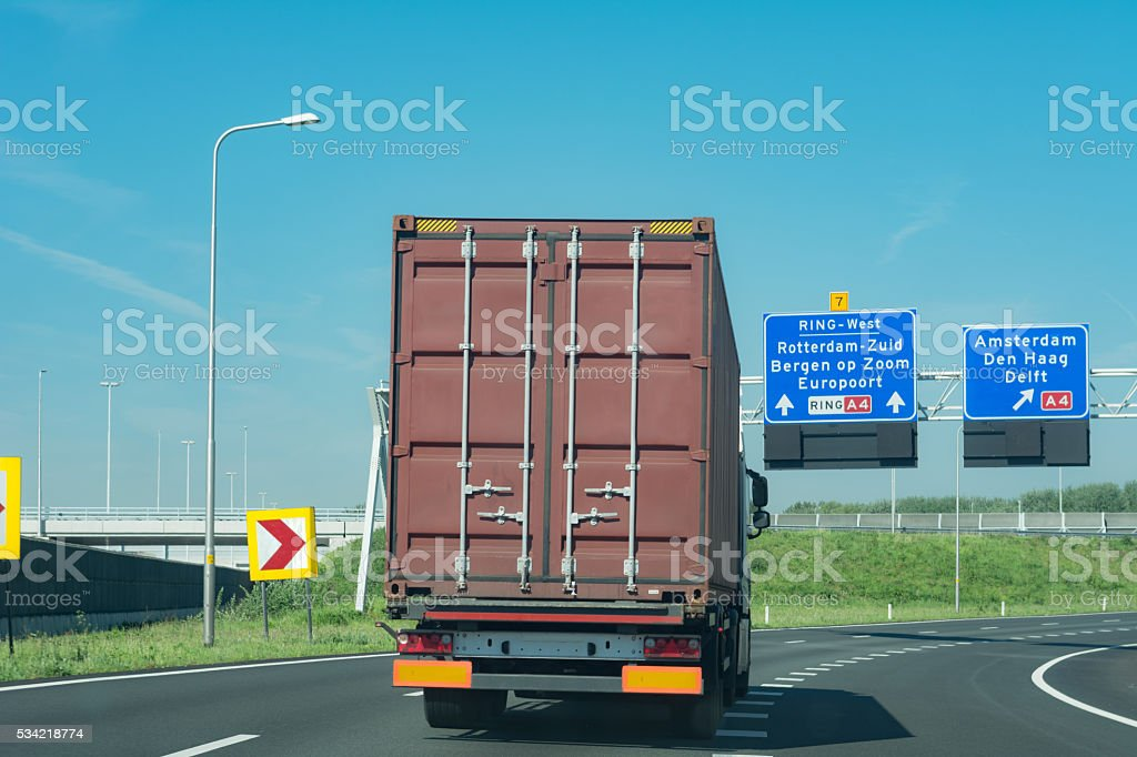 Driving behind brown sea container to europort rotterdam stock photo