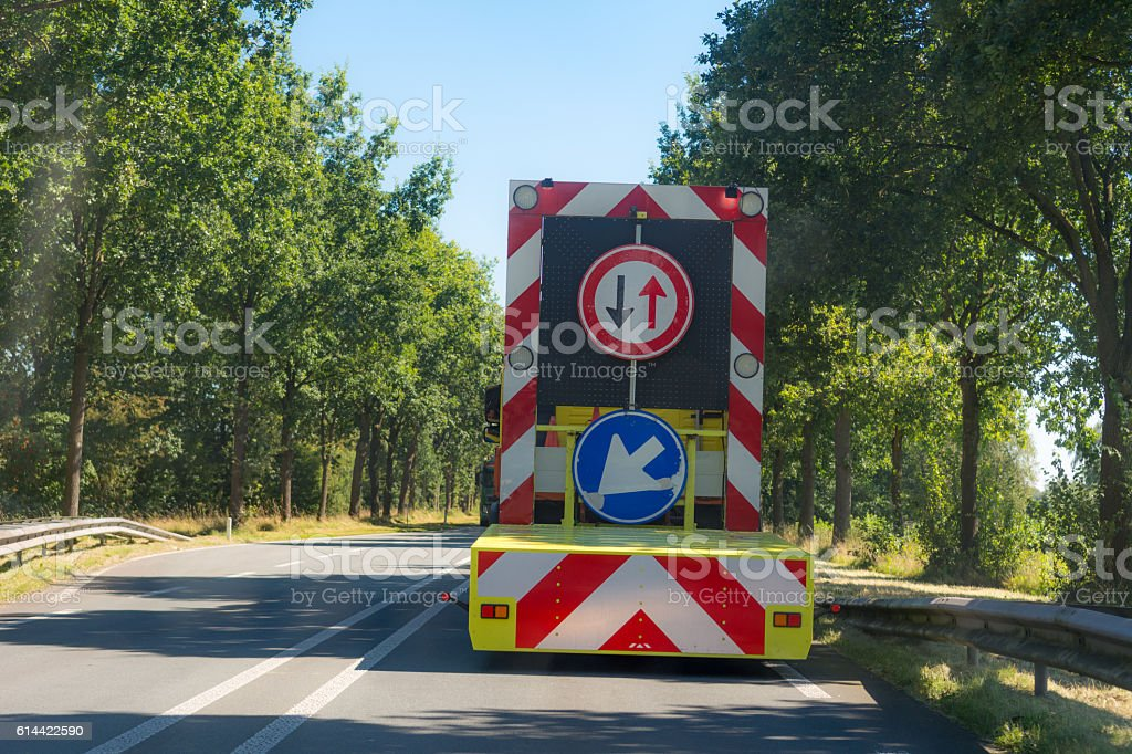 Driving behind roadwork vehicle over road with continuous lane lines stock photo