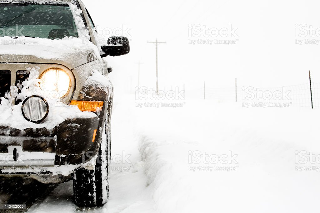 A SUV driving down a snowy road stock photo