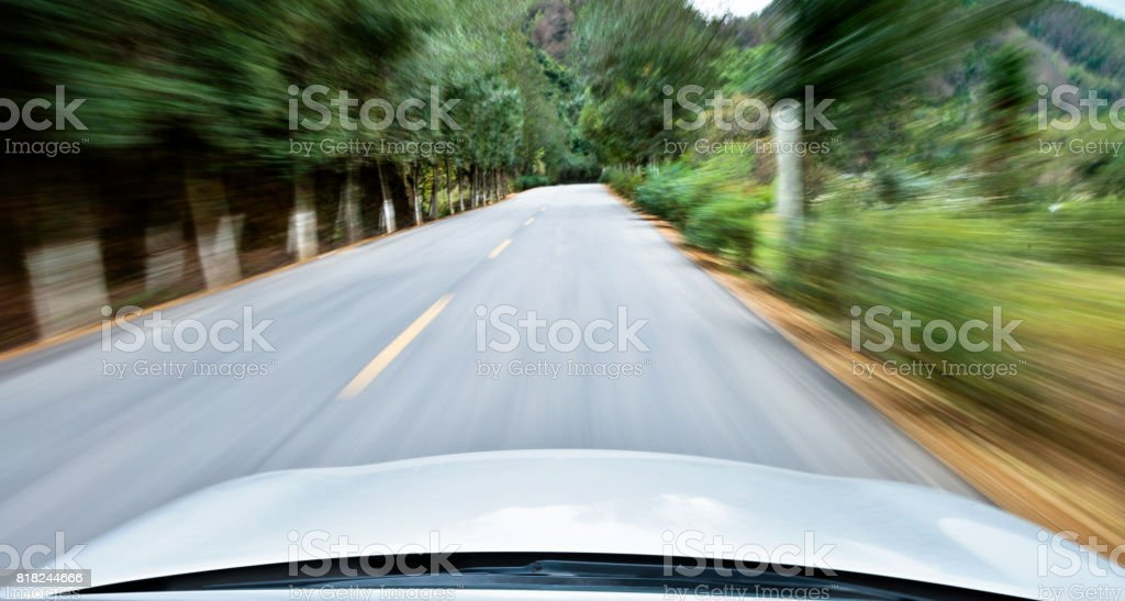 Driving fast along country road stock photo