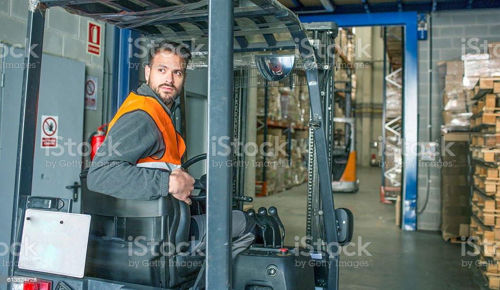Driving fork lift trucks in warehouse stock photo