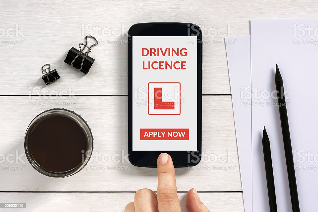 Driving licence app mock-up on smartphone screen with office objects stock photo
