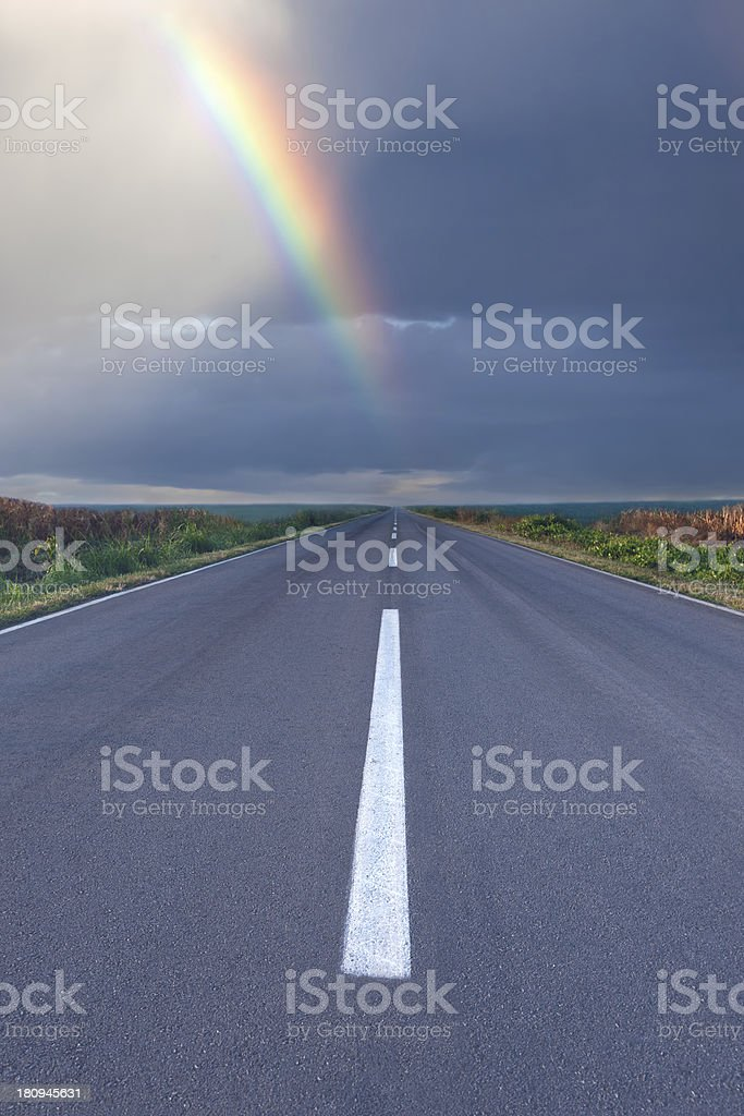 Driving om empty road under the rainbow stock photo