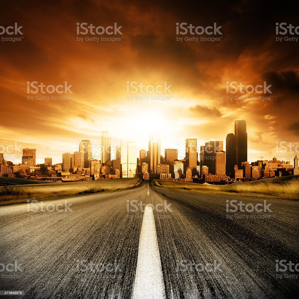 Driving on a road into a city dramatically lit by the sun stock photo