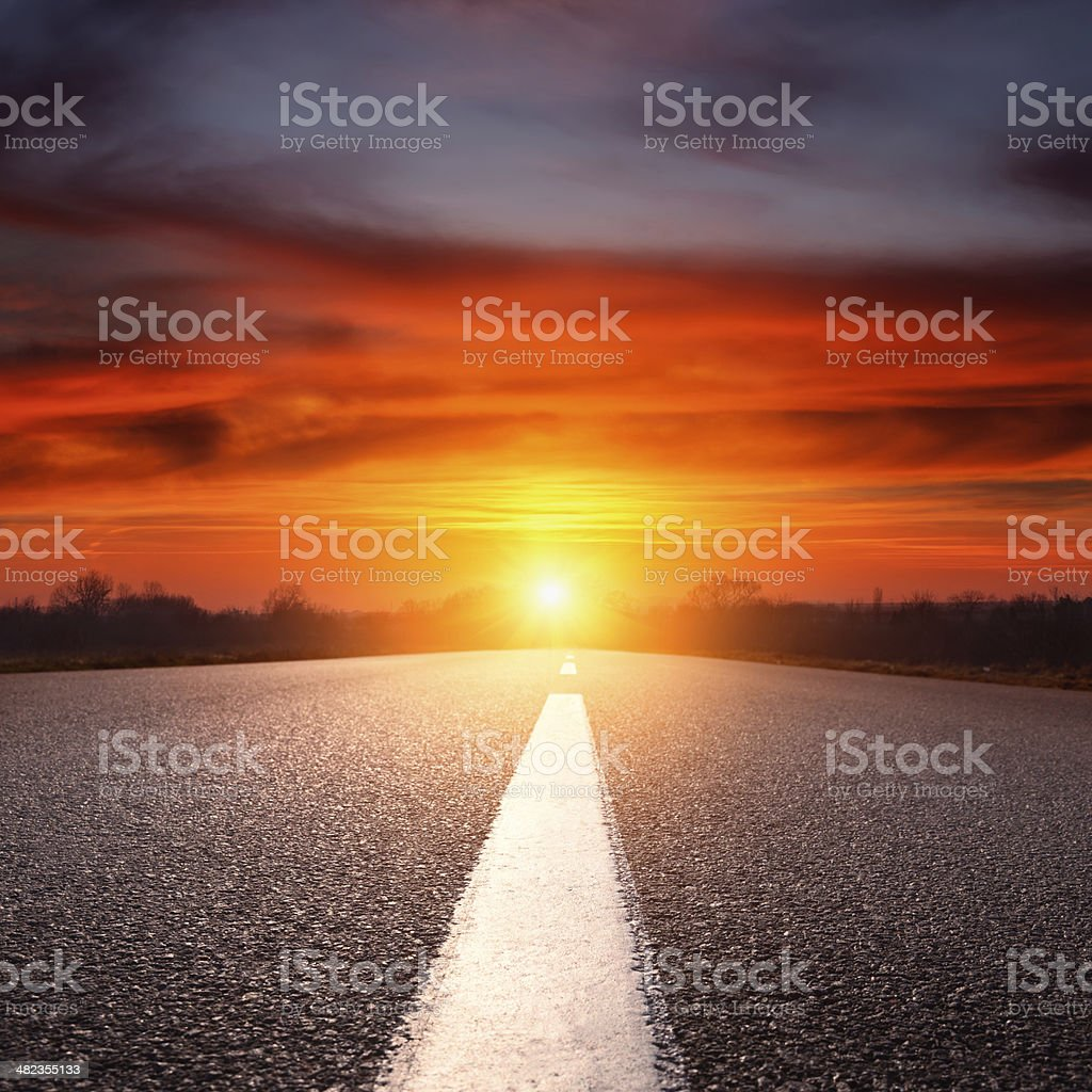 Driving on an empty asphalt highway towards the setting sun stock photo