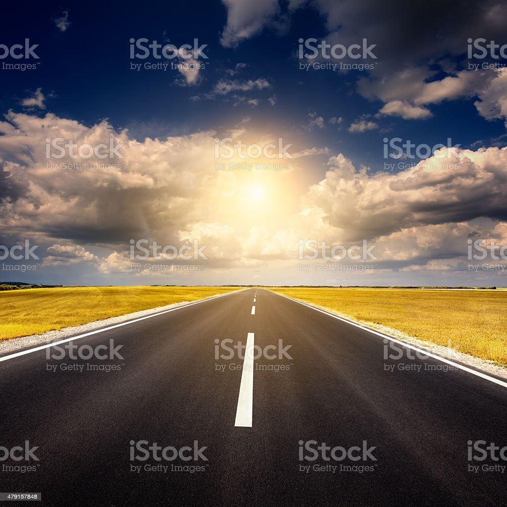 Driving on an empty new asphalt road at sunset stock photo