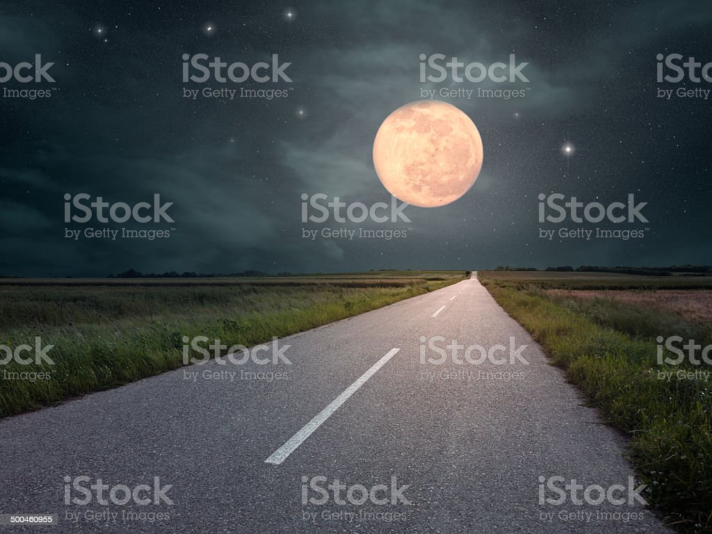 Driving on an empty road towards the moon stock photo