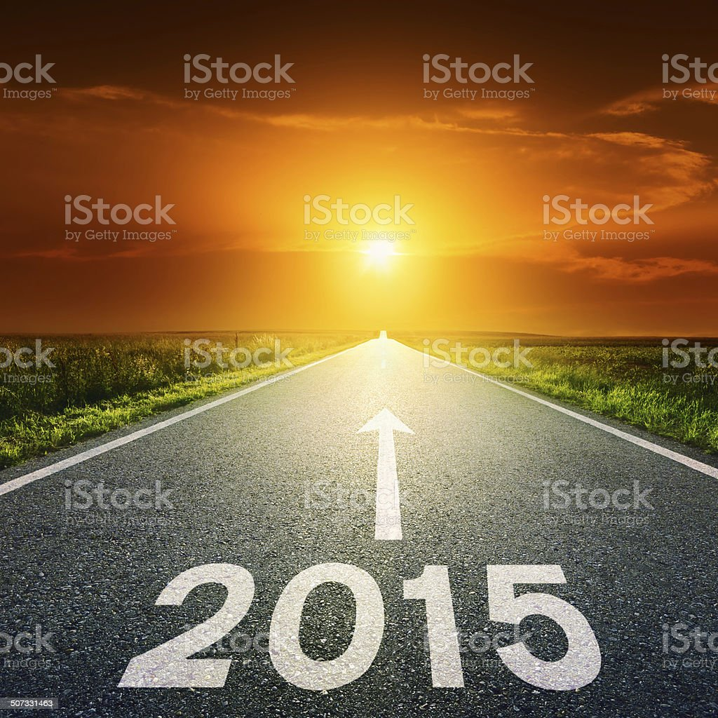 Driving on an empty road towards the sun to 2015 stock photo