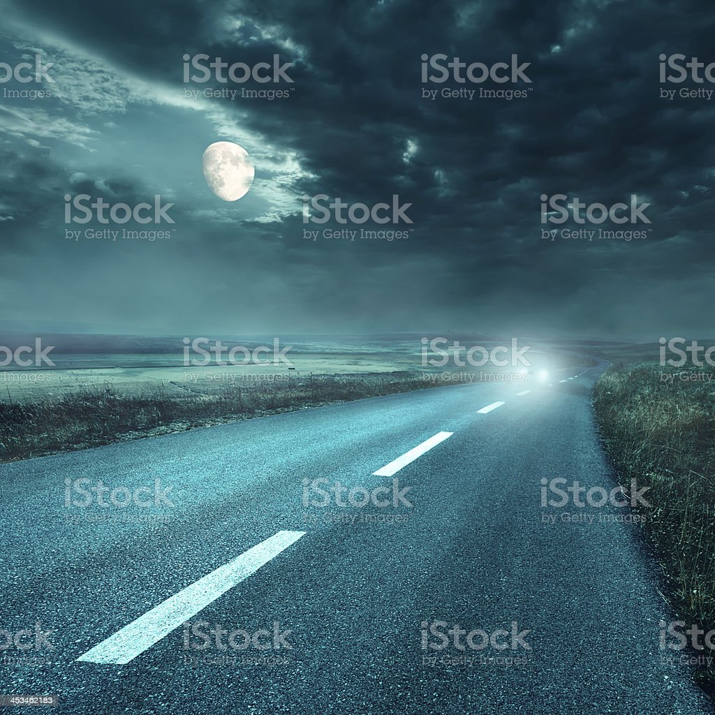 Driving on asphalt road at night towards the headlights stock photo