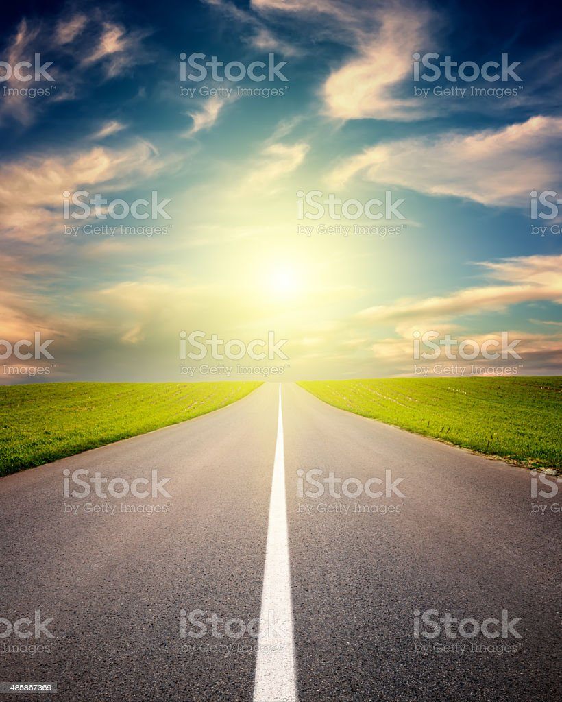 Driving on asphalt road towards the setting sun stock photo