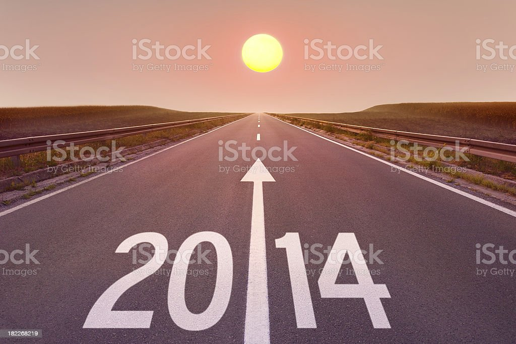 Driving on empty road towards the setting sun 2014 stock photo
