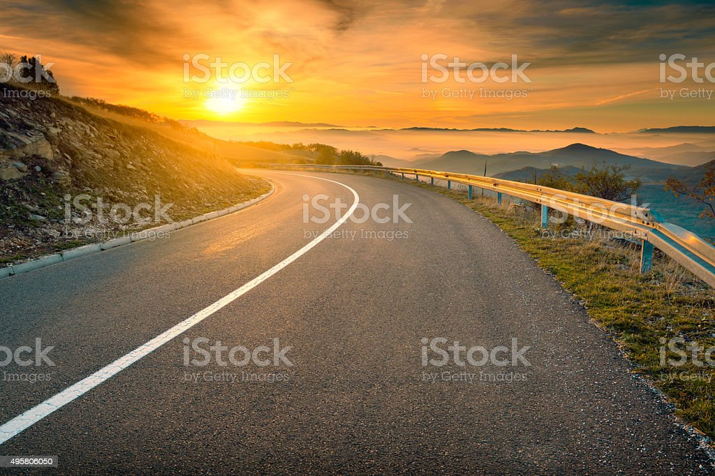 Driving on mountain road against the rising sun stock photo