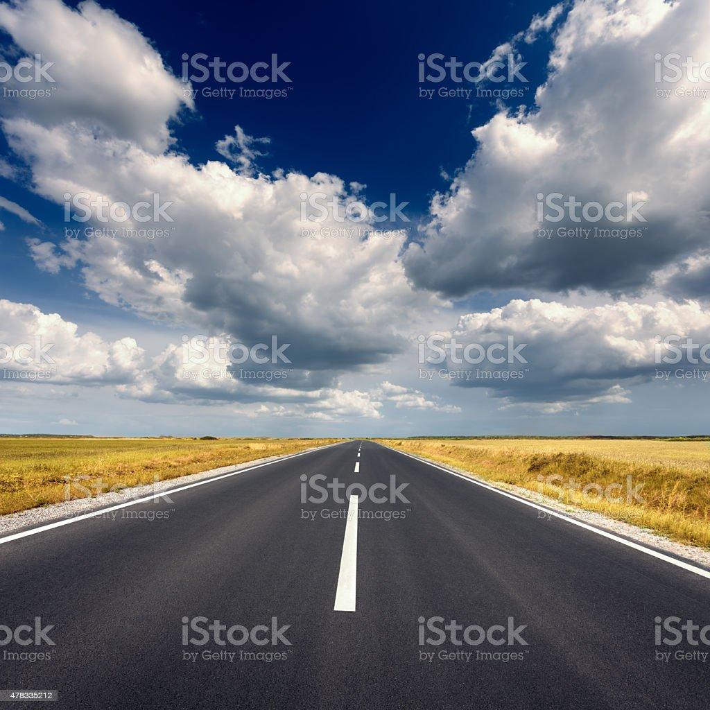 Driving on straight asphalt road at idyllic sunny day stock photo