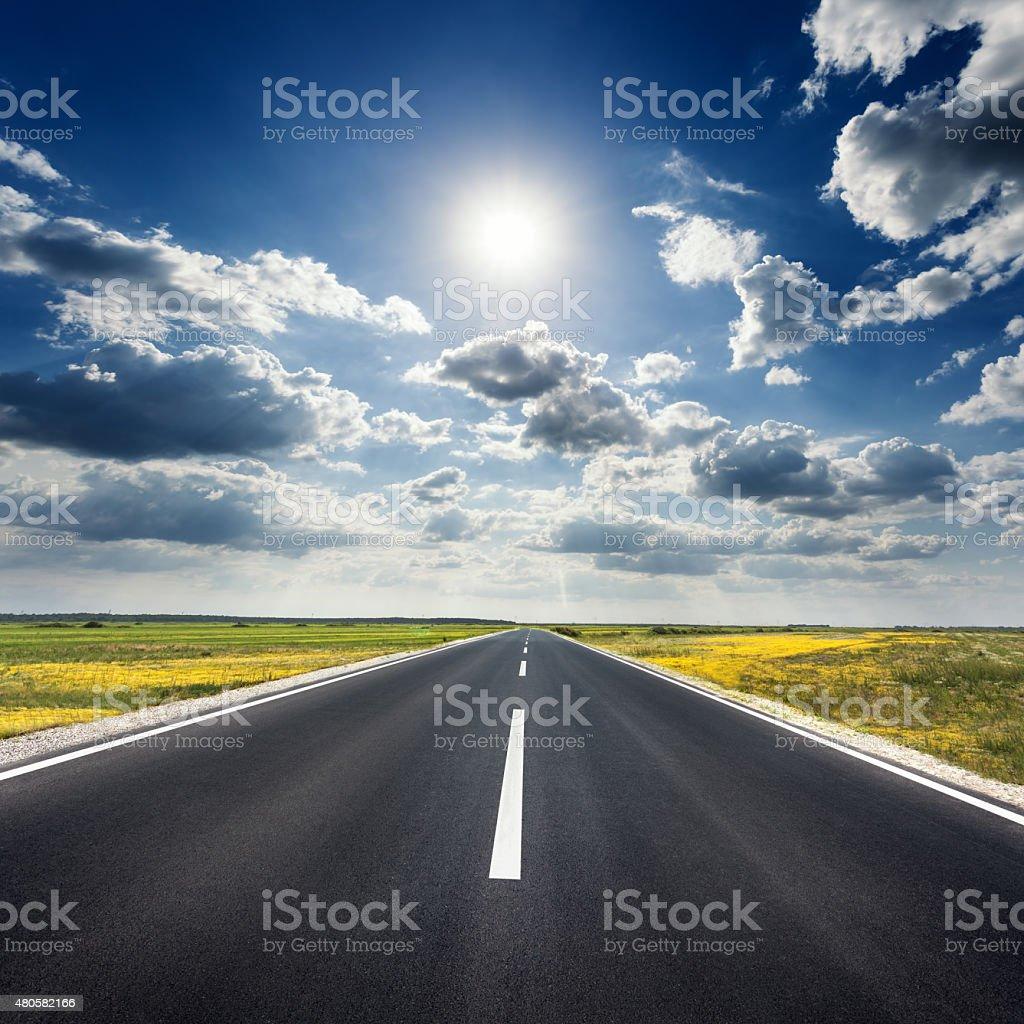 Driving on straight asphalt road towards the sun stock photo