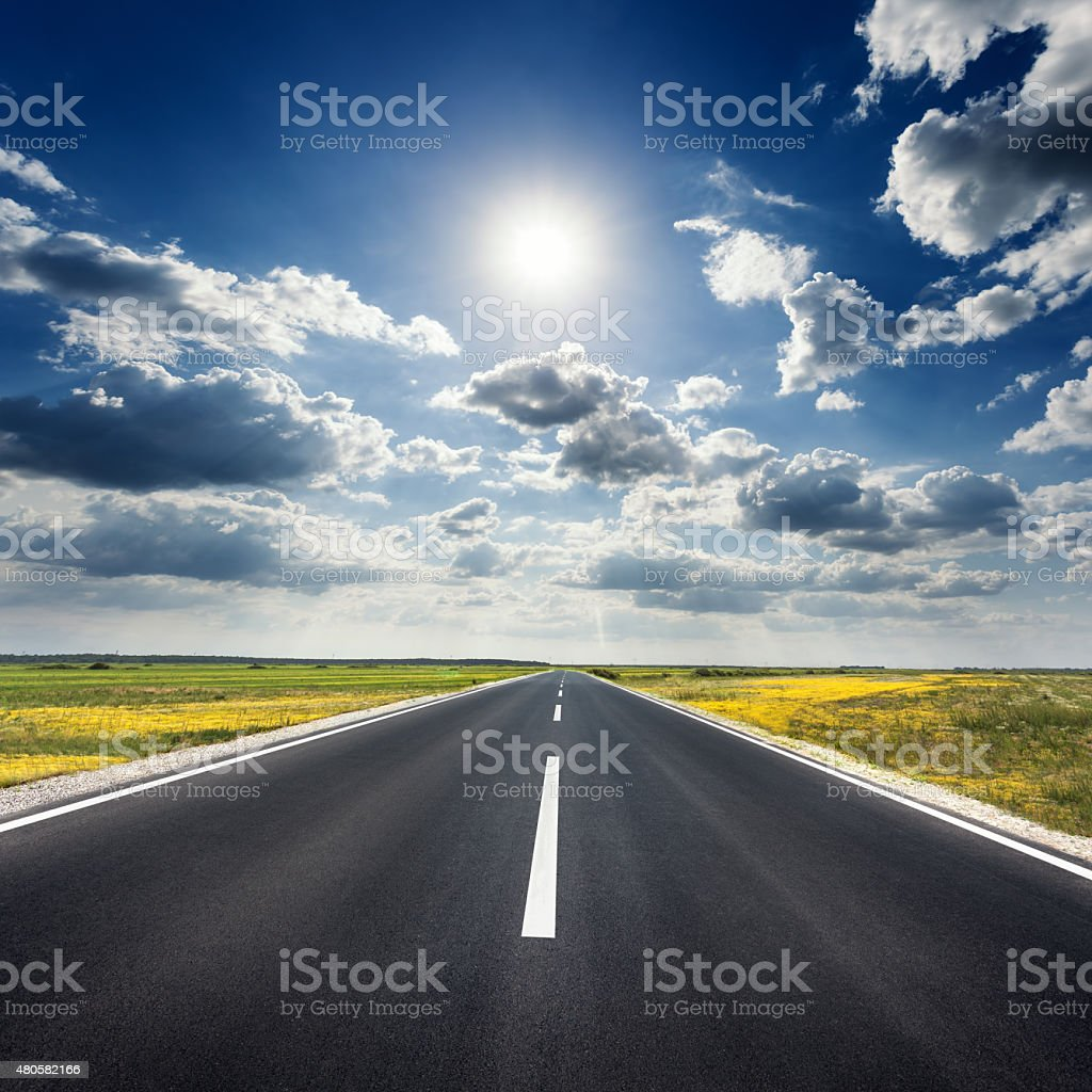 Driving on straight asphalt road towards the sun stock photo