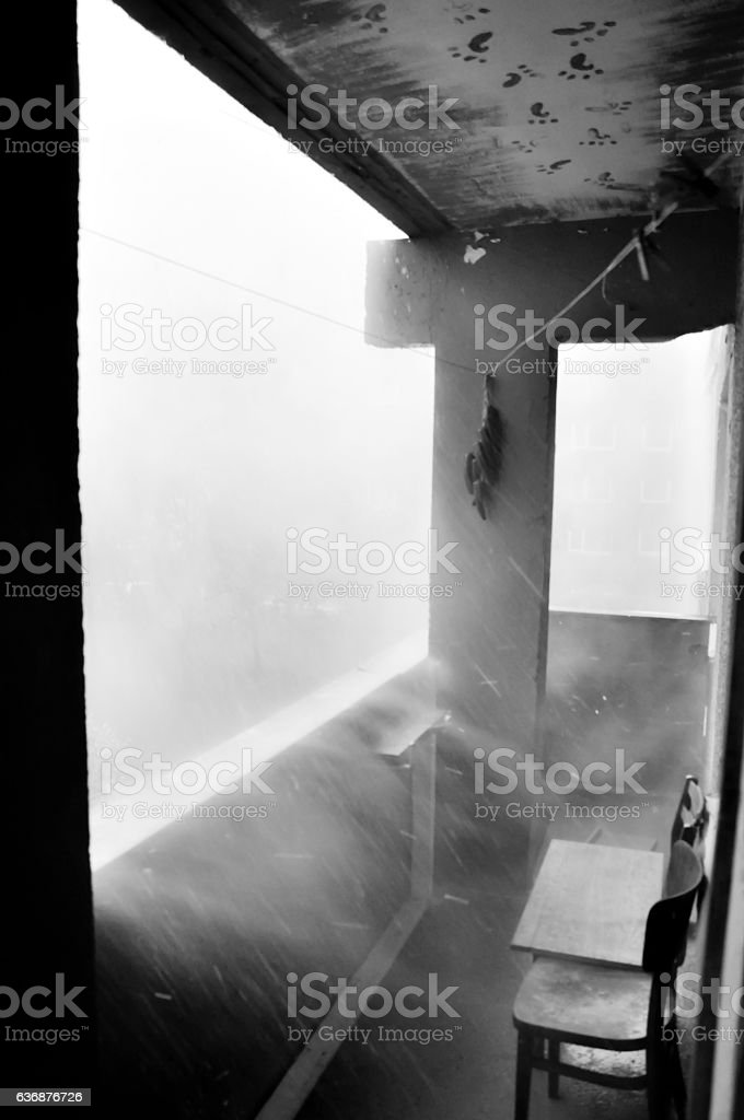 Driving, pouring, pelting rain. Shower thunderstorm. Squally wind storm. Balcony. stock photo